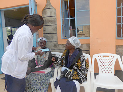 A doctor consults with two patients at the medical clinic in Kenya.